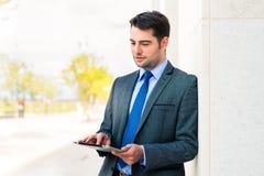 Überzeugter Geschäftsmann im Freien unter Verwendung des Telefons Lizenzfreies Stockfoto