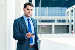Überzeugter Geschäftsmann im Freien unter Verwendung des Telefons Stockfotos