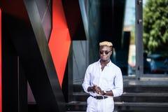 Überzeugter Geschäftsmann Überzeugter junger afroer-amerikanisch Mann, der draußen mit moderner Stadt im Hintergrund steht lizenzfreie stockfotos