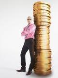 Überzeugter Geschäftsmann Leaning Against Pile von Münzen lizenzfreie stockbilder