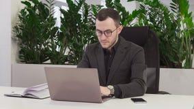 Überzeugter Geschäftsmann mit Gläsern unter Verwendung eines Laptops stock video