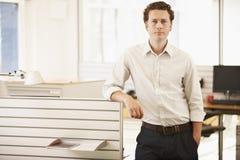 Überzeugter Geschäftsmann Standing By Cubicle Stockfotos