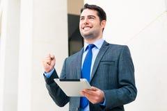 Überzeugter Geschäftsmann unter Verwendung des Tablet-Computers Stockfoto