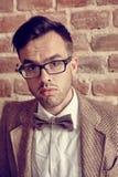 Überzeugter hübscher junger Mann, der gegen einen Ziegelstein steht Stockfoto