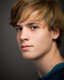 Überzeugter jugendlicher blonder junger Mann im Studio Stockbild