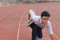 Überzeugter junger asiatischer Geschäftsmann mit der bereiten Position des Laptops auf Rennstrecke nachzuschicken Anfangs, lizenzfreies stockbild