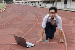 Überzeugter junger asiatischer Geschäftsmann mit der bereiten Position des Laptops auf Rennstrecke nachzuschicken Anfangs, Vergrö stockfotografie