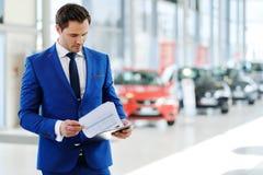 Überzeugter junger Autohändler, der im Ausstellungsraum steht lizenzfreie stockfotos