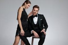 Überzeugter junger Bräutigam, der sitzt und von seiner Freundin getröstet wird lizenzfreie stockfotos