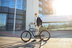 Überzeugter junger Geschäftsmann, der mit Fahrrad auf der Straße in der Stadt geht Stockfotos