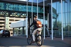 Überzeugter junger Geschäftsmann, der mit Fahrrad auf der Straße in der Stadt geht Lizenzfreie Stockfotos