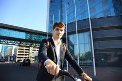 Überzeugter junger Geschäftsmann, der mit Fahrrad auf der Straße in der Stadt geht Lizenzfreie Stockbilder