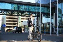Überzeugter junger Geschäftsmann, der mit Fahrrad auf der Straße in der Stadt geht Stockbild
