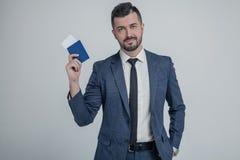 Überzeugter junger Geschäftsmann im klassischen schwarzen Anzug, Hemdgriffpaß, Bordkartekarte herein lokalisiert auf grauem Wandh stockfotografie