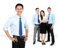 Überzeugter junger Geschäftsmann und Geschäft team als Hintergrund Stockfotos