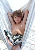 Überzeugter junger Junge, der in der Hängematte auf Ferien sitzt Lizenzfreie Stockfotografie