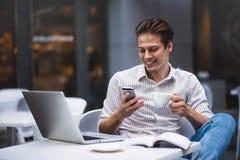 Überzeugter junger Mann in der intelligenten Freizeitkleidung, die eine Schale hält und durch Smartphone spricht stockbilder