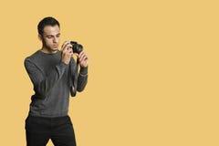 überzeugter junger Mann mit Digitalkamera über farbigem Hintergrund Lizenzfreie Stockbilder