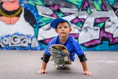Überzeugter kleiner Junge, der auf einem Skateboard spielt Stockbild