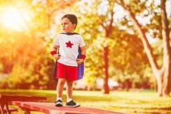 Überzeugter kleines Kinderjunge spielt Superhelden stockbild