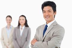 Überzeugter lächelnder Geschäftsmann mit seinem Team hinter ihm Lizenzfreies Stockbild