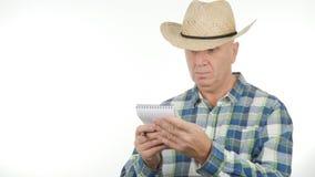 Überzeugter Landwirt Write In Pocketbook unter Verwendung eines Stiftes lizenzfreie stockfotografie