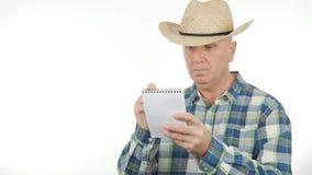 Überzeugter Landwirt Write In Pocketbook unter Verwendung eines Stiftes stockfotos