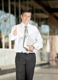 Überzeugter Lehrer With Books Gesturing Thumbsup an Lizenzfreie Stockfotos