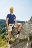 Überzeugter männlicher Bergsteiger, der auf Felsen steht Stockbild