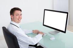 Überzeugter männlicher Doktor, der an Computer am Schreibtisch arbeitet Stockbild