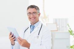 Überzeugter männlicher Doktor, der Tablet-Computer verwendet Stockfoto