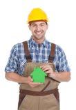 Überzeugter männlicher Erbauer, der Modell des grünen Hauses hält Stockfoto