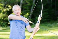 Überzeugter männlicher Pfeil Archers Holding Bow And im Wald Stockfotografie