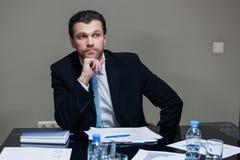 Überzeugter Mann bei Tisch Lizenzfreies Stockfoto
