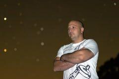 Überzeugter Mann mit den Armen kreuzte Stellung gegen sternenklare Nacht Stockfotografie