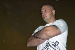 Überzeugter Mann mit den Armen kreuzte Stellung gegen sternenklare Nacht Stockfoto