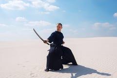 Überzeugter Mann mit einer Klinge in seinen Händen steht in der niedrigen Position Lizenzfreies Stockfoto