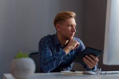 Überzeugter Mann mit Tablette im Büro Lizenzfreie Stockfotos