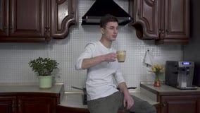 Überzeugter Mann nimmt Tasse Kaffee-Cappuccino von der Tabelle, geht zum Ofen und sitzt auf ihm und herein trinkt Getränk stock video footage