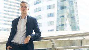 überzeugter Mannstand des intelligenten Geschäfts am öffentlichen Platz im Freien Lizenzfreie Stockbilder
