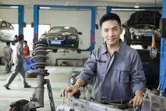 Überzeugter Mechaniker Fixing Car Engine, Kamera betrachtend Lizenzfreies Stockbild
