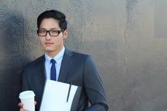 Überzeugter moderner Geschäftsmann mit den Gläsern, die halten, um zu gehen Tasse Kaffee und Ordner mit Dokumenten Lizenzfreies Stockfoto