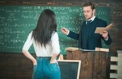 Überzeugter Professor, der Erklärungen beim Halten des Buches und der Gläser in seinen Händen gibt Mädchen der hinteren Ansicht m stockbild