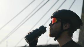 Überzeugter Radfahrer mit Trinkwasser des roten Bartes von tragendem Sturzhelm und Sonnenbrille der Flasche Brücke und Fluss im H stock footage