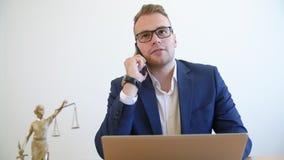 Überzeugter Rechtsanwalt, der Beratung durch einen Smartphone macht stock video