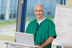 Überzeugter reifer Chirurg Standing At Podium Stockbild