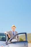 Überzeugter reifer Herr mit dem Hut, der nahe bei seinem automobil aufwirft Lizenzfreie Stockfotos