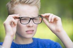 Überzeugter Teenager mit den Gläsern im Freien Stockbilder