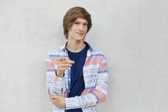 Überzeugter Teenager mit der stilvollen Frisur, die zufälliges Hemd zeigend mit seinem Finger auf Kamera beim Zeigen etwas trägt  Lizenzfreies Stockfoto