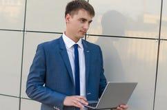 Überzeugter und erfolgreicher Geschäftsmann, der einen Laptop hält lizenzfreies stockbild